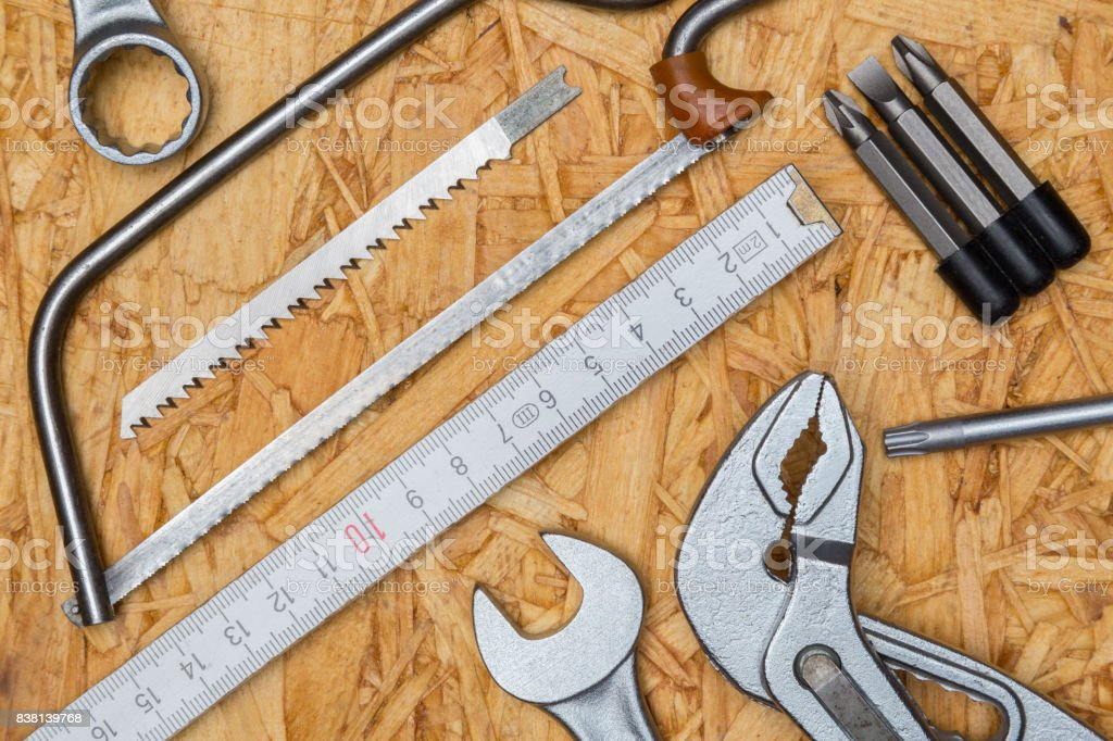 Tool concept, pliers, tine, saw, wrench on wooden plate and bird perspective stock photo