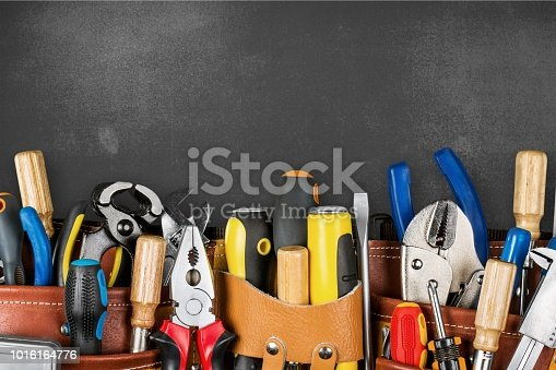 Tool belt with tools on wooden background
