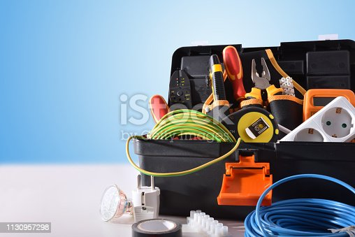 Toolbox full of tools and electrical equipment on white table and blue isolated background. Front view. Horizontal composition.