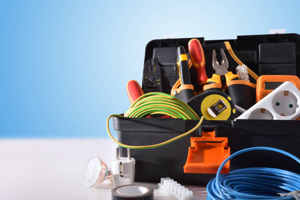 Toolbox full of tools and electrical equipment on white table Toolbox full of tools and electrical equipment on white table and blue isolated background. Front view. Horizontal composition. power occupation stock pictures, royalty-free photos & images