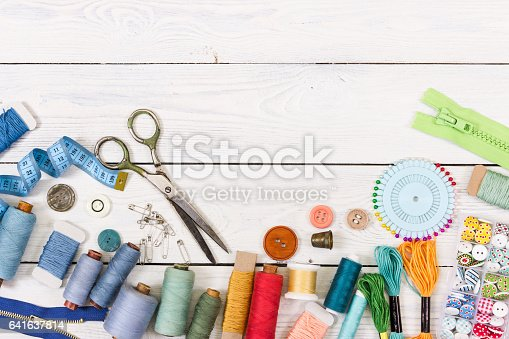 Tools and accessories for sewing on light wooden background. Top view.