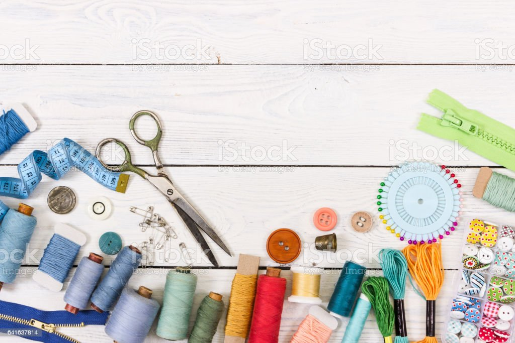 Tools and accessories for sewing on light wooden background. stock photo