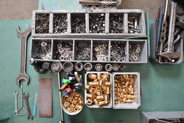 werkzeuge und sortierte bauteile auf dem desktop in der fabrik - keller organisieren stock-fotos und bilder