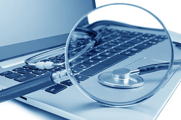 Tools for diagnostics on the laptop. Through a magnifying glass. stock photo