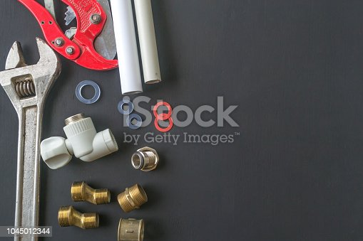 Tools for repair of water supply systems on a black background.
