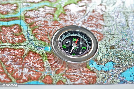 97623256istockphoto Tools for the journey - map and compass. 523050086