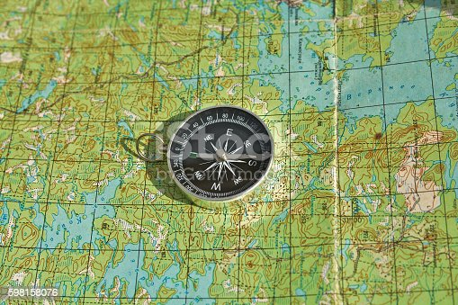 97623256istockphoto Tools for the journey - map and compass. 598158076