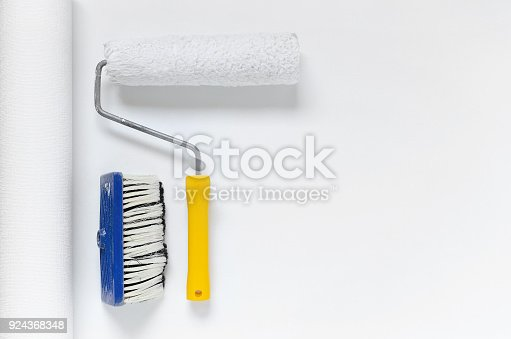 835790922istockphoto tools for wallpapering, paint roller and a brush on white wallpaper roll with copy space 924368348