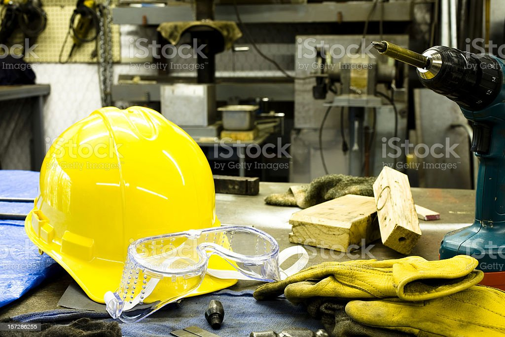 Tools, gloves, hardhat and goggles are on the bench. stock photo