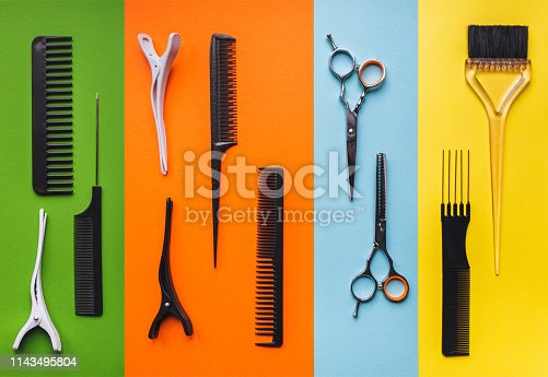 696318954 istock photo Tools hairdresser on the background of pastel paper in the form of multi-colored stripes. Barbershop. 1143495804