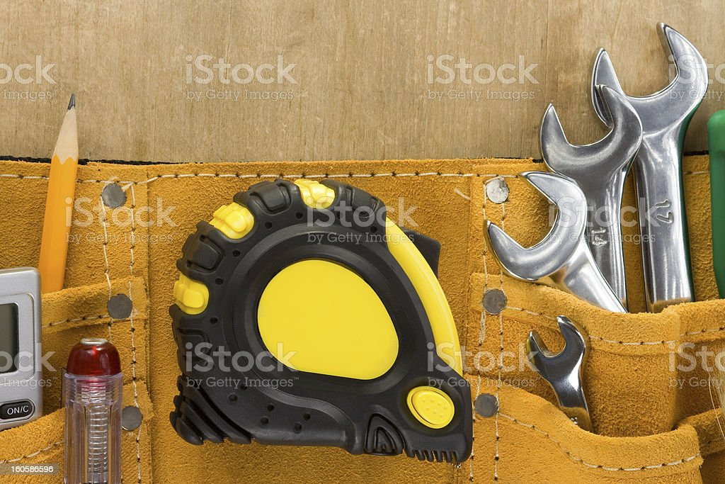 tools in construction belt on wooden background royalty-free stock photo