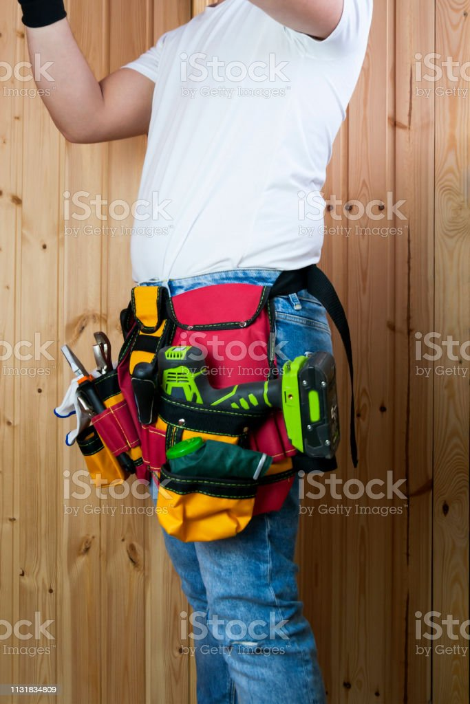 Tools in the belt for tools. The builder is holding a tool. Selective...