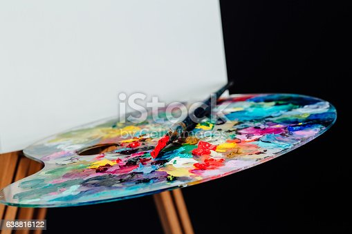 istock Tools of the artist. Brushes, wooden easel tripod, palette colorful 638816122