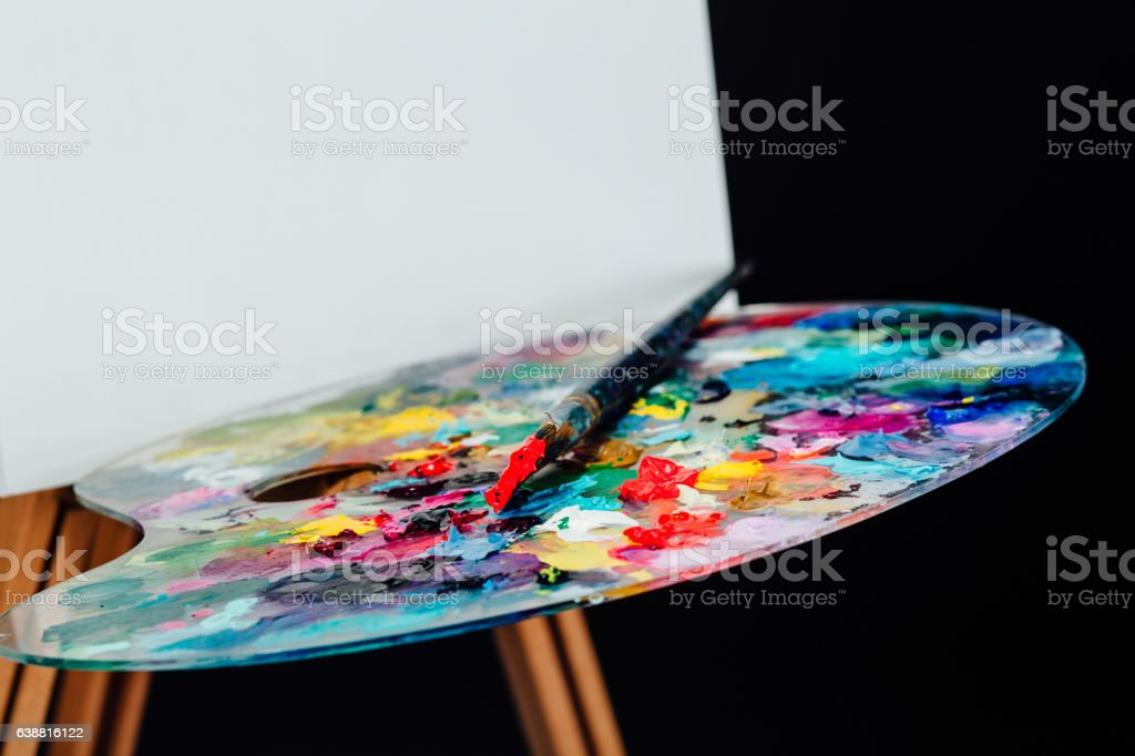 Tools of the artist. Brushes, wooden easel tripod, palette colorful stock photo