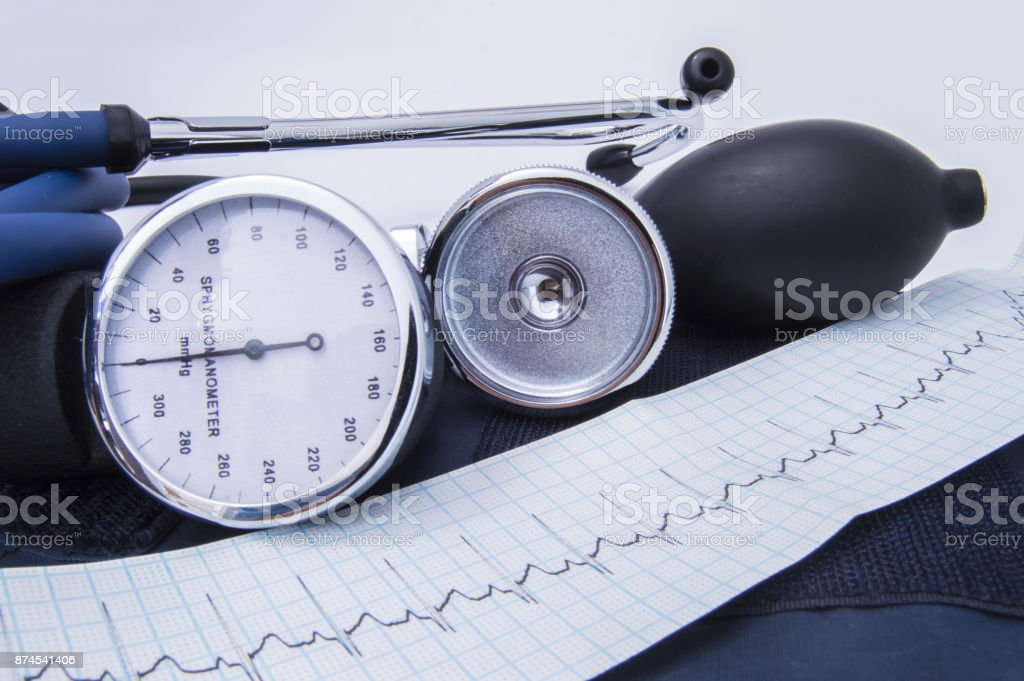 Tools or instruments for diagnosis in internal medicine: stethoscope, aneroid sfigmomanometr with bulb and tape with the recorded electrocardiogram (EKG or ECG)  lie on the cuff in the doctor's Office stock photo