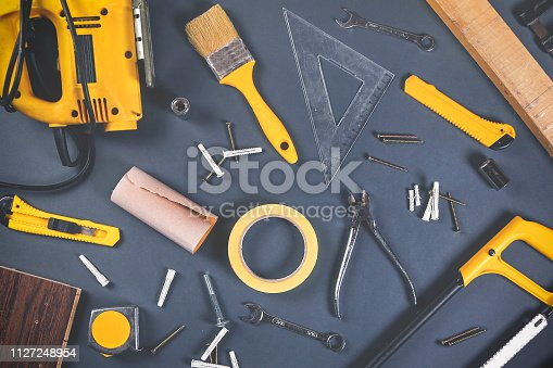 Group of woodwork and carpentry work tools (electric saw, hardhat, paintbrush, wrench, scalpel, scotch tape, dowel, clamp, screw, hammer, hand saw) on gray background.