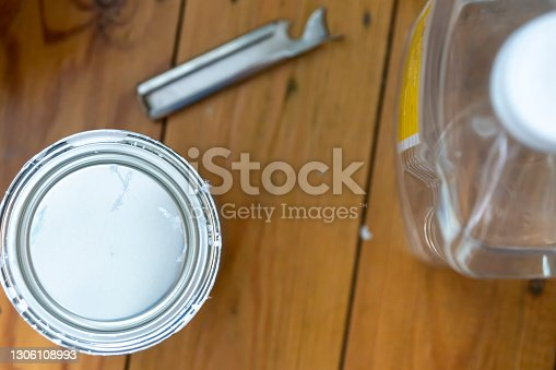 DIY tools. White spirit bottle, paint tin and tin opener ready for DIY, they are on a polished wooden floor.
