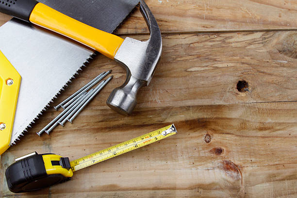 """Tools """"Hammer, saw, nails and tape measure on wood"""" nail work tool stock pictures, royalty-free photos & images"""