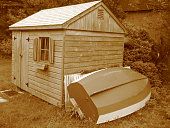 Toolshed, little house with rowboat in Maine in sepia tone. retro-looking.