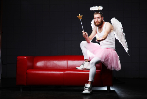Humorous male  tooth fairy sitting on the arm of a couch with wand and giant molar.  Dark background and red couch.