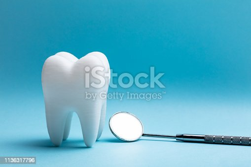 Close-up Of Tooth With Dental Mirror Over Blue Background