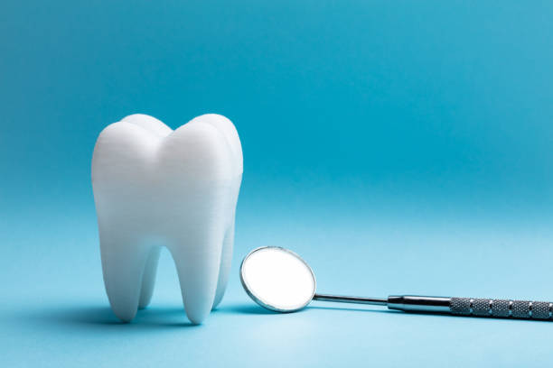 Tooth With Dental Mirror Close-up Of Tooth With Dental Mirror Over Blue Background dental health stock pictures, royalty-free photos & images