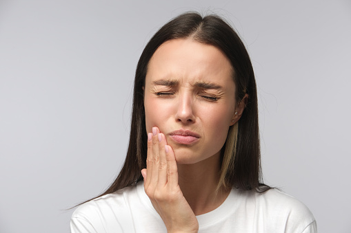 Toothache concept. Studio shot of young female feeling pain, holding her cheek with hand, suffering from bad tooth ache
