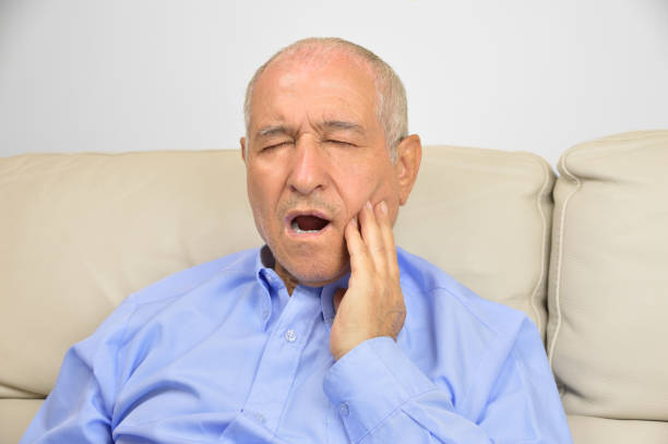 Toothache Toothache. Frustrated senior touching his cheek and keeping eyes closed while sitting on the couch at home clenching teeth stock pictures, royalty-free photos & images