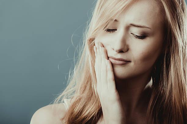 dolor de muelas. mujer que sufre de dolor de diente - mandibula fotografías e imágenes de stock