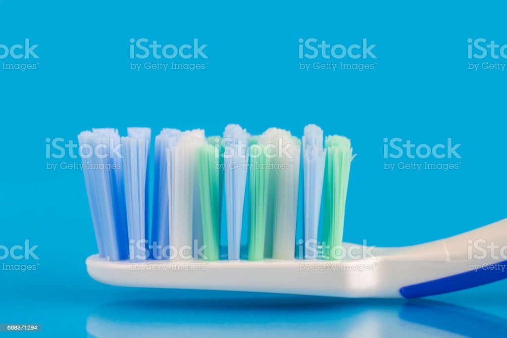 Toothbrush head on blue background, macro image. stock photo