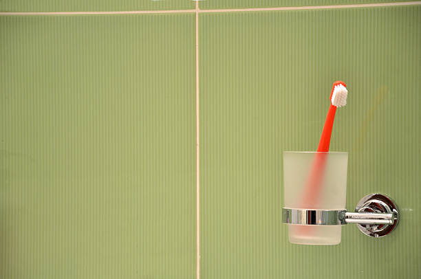 Toothbrush in glass in metal holder fixed to green tile - foto de stock