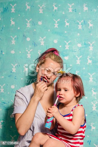 185211538istockphoto Toothbrush. Mom teaches a little daughter to brush their teeth 871235484