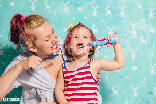 800444456 istock photo Toothbrush. Mom teaches a little daughter to brush their teeth 871235606