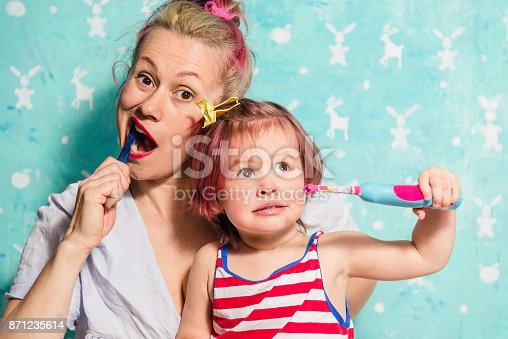 istock Toothbrush. Mom teaches a little daughter to brush their teeth 871235614
