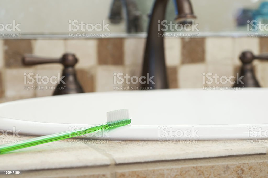 Toothbrush Resting on Edge of Sink royalty-free stock photo