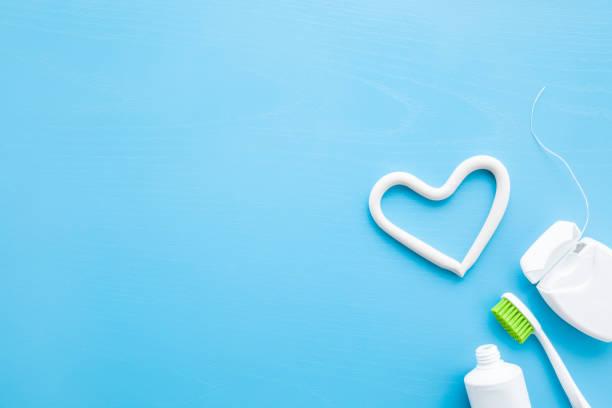 zahnbürste, weißes rohr aus zahnpasta, behälter mit zahnseide auf pastellblauem hintergrund. herzform aus paste. liebe gesunde zähne konzept. leerer platz für text, zitat, sprüche oder logo. - zahnarztausrüstung stock-fotos und bilder