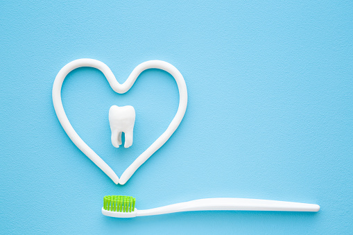 istock Toothbrush with green bristles on pastel blue background. Heart shape created from paste. White tooth in middle of heart. Love healthy teeth. Empty place for text, quote, sayings or logo. Closeup. 1143929500