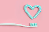 istock Toothbrushes and turquoise color toothpaste in shape of heart on pink background. Dental and healthcare concept. 1001482074