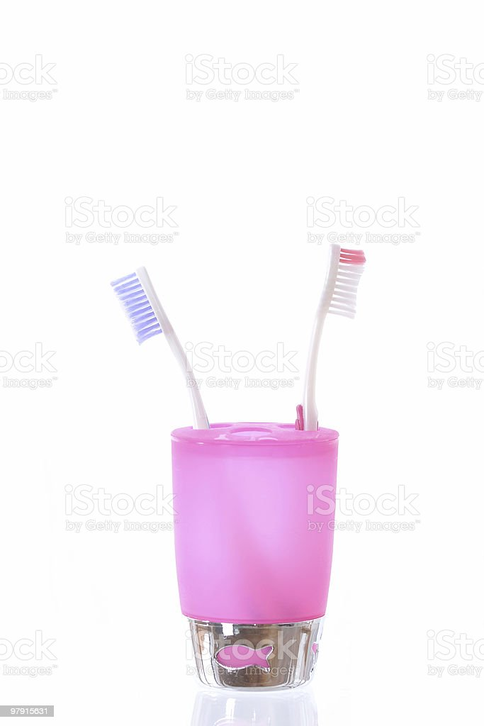 Toothbrushes in a pink cup holder royalty-free stock photo
