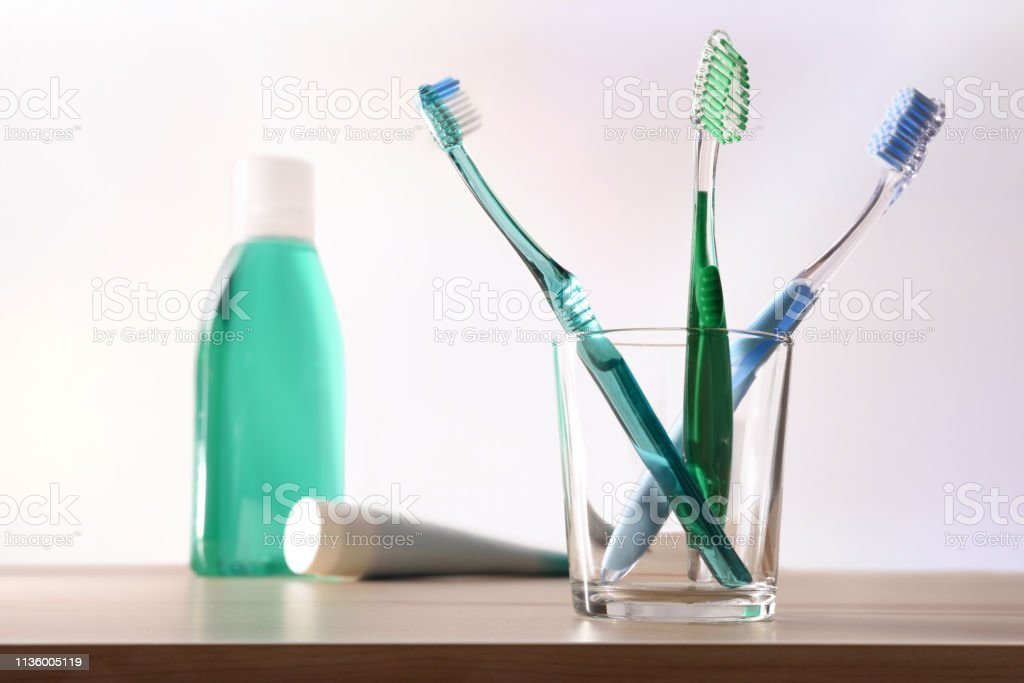 Toothbrushes in glass cup on table and toothpaste and mouthwash stock photo