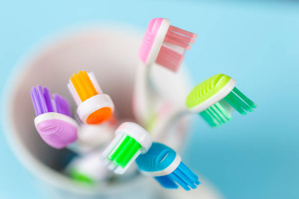 toothbrushes close up shot of toothbrushes in a cup on a blue background toothbrush stock pictures, royalty-free photos & images