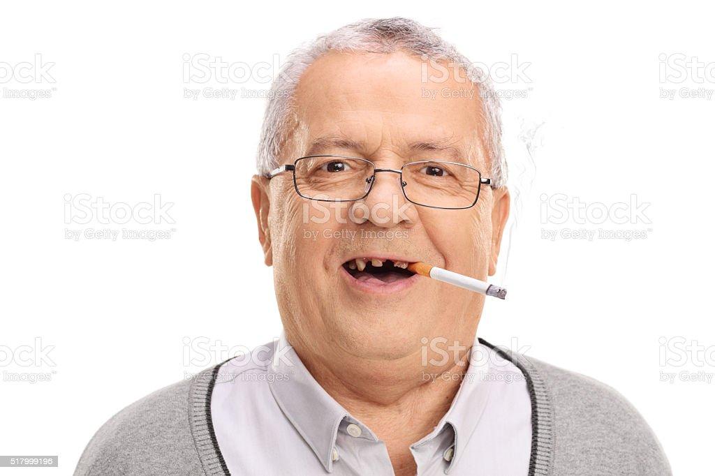 Toothless senior smoking a cigarette stock photo