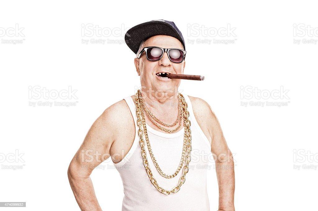 Toothless senior with a hip-hop cap smoking cigar stock photo