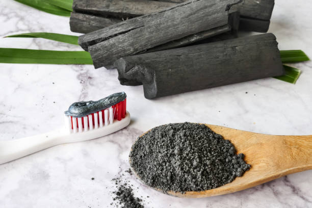 Toothpaste by activated charcoal powder on marble table stock photo