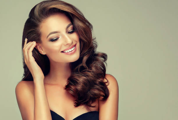 Toothy smile on the face of young, brown haired woman with voluminous hair. stock photo
