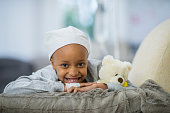 A young girl of African descent is indoors in a hospital room. She has cancer, and she is wearing a hat. She is lying in bed with her teddy bear while hooked up to an IV. She is smiling at the camera.