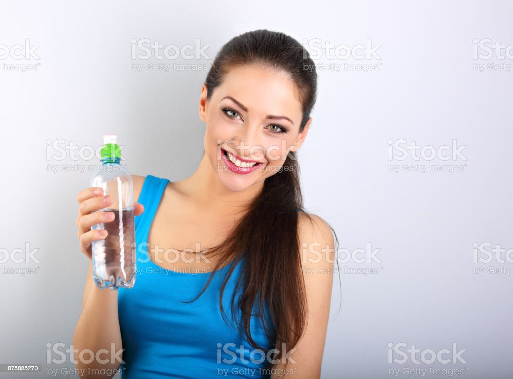 Toothy smiling happy beautiful woman holding the bottle of pure water on blue background. Heathy body and skin. stock photo