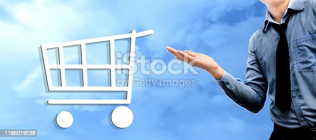 istock A too-young businessman wearing a blue colored shirt and black tie and holding something in hand without a theme. Isolated on blue colored sky background. With a trolly icon, the concept of marketing. 1166019238
