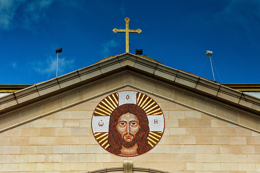 A mosaic of Jesus Christ and a Cross adorn the top of this beautiful old Christian Church. Against a very blue sky