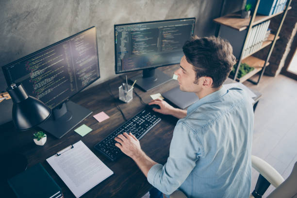 Top above high angle view portrait of his he nice attractive focused skilled geek guy typing bug track report cyberspace security at modern industrial interior style concrete wall work place station stock photo